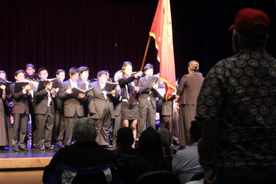 Highly esteemed veteran stands as choir sings in honor of marines.
